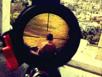 جندي إسرائيلي يصوّر عدسة بندقيته